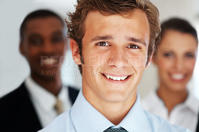 Buy stock photo Closeup of a businessman standing smiling in front of team at office