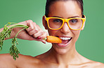 Young woman wearing glasses while eating fresh carrot