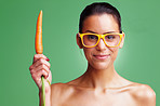 Girl wearing glasses and holding carrot against green background