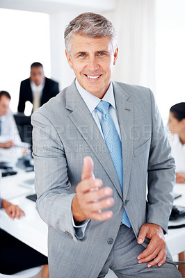 Buy stock photo Portrait of a senior manager offering a handshake with his team working in background