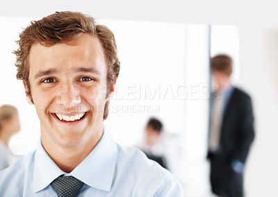 Buy stock photo Successful male business executive smiling with colleagues working in background
