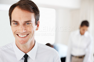 Buy stock photo Happy young male business executive at office with colleagues in background
