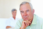 Thoughtful mature man with woman in background