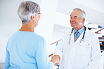 Mature doctor and woman shaking hands