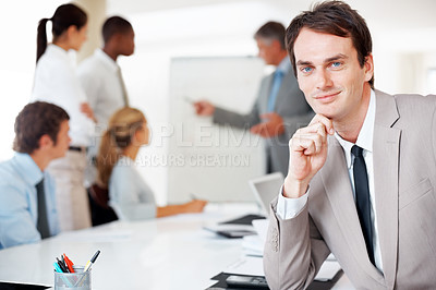 Buy stock photo Portrait of a young businessman with his colleagues in background during a business presentation