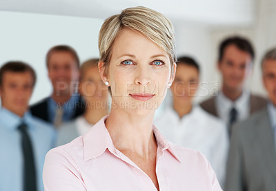 Buy stock photo Portrait of a confident young businesswoman with her team in background