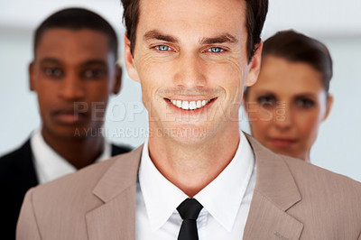 Buy stock photo Portrait of a successful young businessman standing with his business colleagues in background