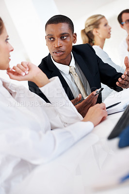 Buy stock photo Smart young african american businessman discussing project with his colleague in a meeting