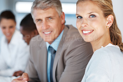 Buy stock photo Portrait of a pretty young businesswoman sitting in a meeting with her colleagues at office