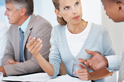 Buy stock photo Portrait of a young businesswoman sitting at a meeting and discussing with colleague