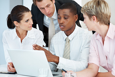 Buy stock photo An african american businessman discussing working ideas with his colleagues at office