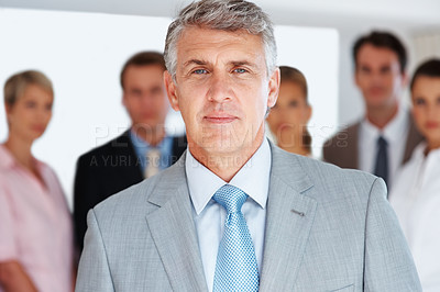 Buy stock photo Portrait of a confident mature businessman standing with colleagues in background