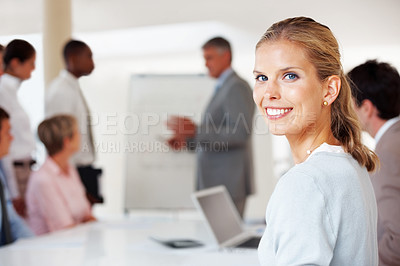 Buy stock photo Charming young businesswoman looking at you during a presentation in board room