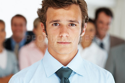 Buy stock photo Closeup portrait of a smart young executive with people in background