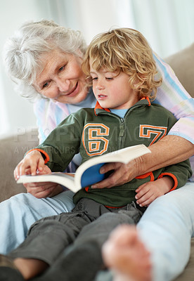 Buy stock photo A small boy and his grandmother reading a book while sitting on the couch