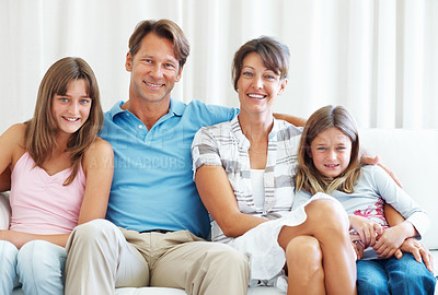 Buy stock photo Cute family of four sitting together on a sofa and smiling