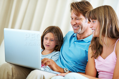 Buy stock photo Father sitting on a sofa with his daughters and browsing the internet