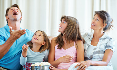 Buy stock photo Family sitting together on a sofa with man tossing popcorn