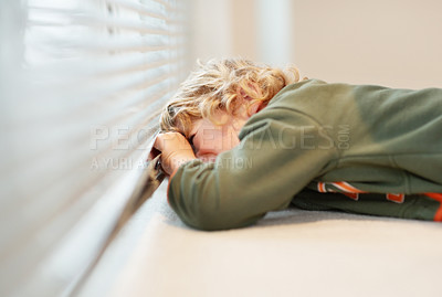 Buy stock photo A young boy peeking through a window