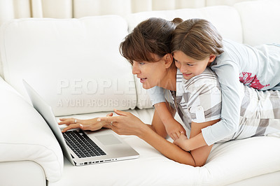 Buy stock photo Mother lying on a sofa using laptop with daughter on top of her
