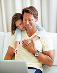 Man and his young daughter using laptop
