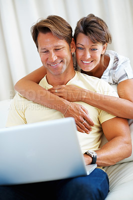 Buy stock photo Man sitting on a sofa browsing internet on laptop with woman hugging him from behind
