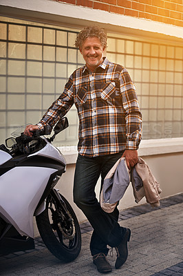 Buy stock photo Portrait of a happy mature man leaning against his motorbike