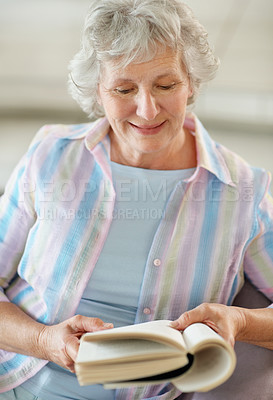 Buy stock photo A happy senior woman reading a book at home