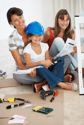 Buy stock photo Portrait of mother and her children sitting together while building a shelf and smiling