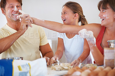 Buy stock photo Family enjoying in the kitchen with girl applying flour to her father's nose