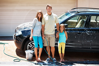 Buy stock photo Full length of man standing with his daughters and smiling while washing car