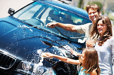 Buy stock photo Portrait of smiling family working together and washing their car