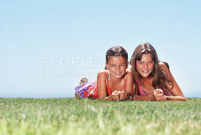 Buy stock photo Portrait of two sisters lying together on grass and smiling - copyspace