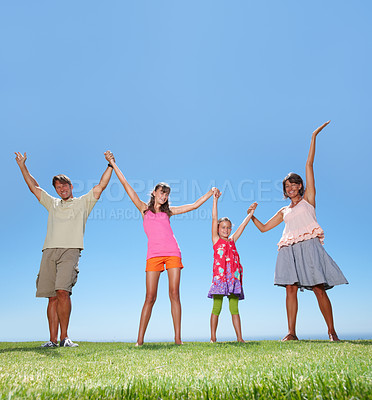 Buy stock photo Full length of family happy family standing on grass and celebrating - copyspace