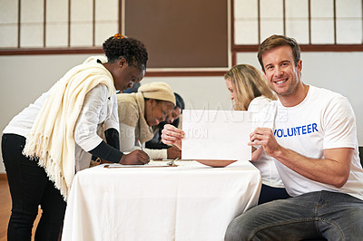Buy stock photo Cropped portrait of a volunteer holding an empty sign while volunteers get signatures in the background
