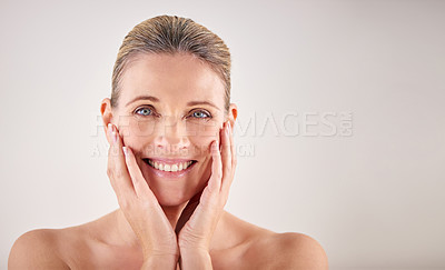 Buy stock photo Cropped studio portrait of an attractive mature woman touching her skin