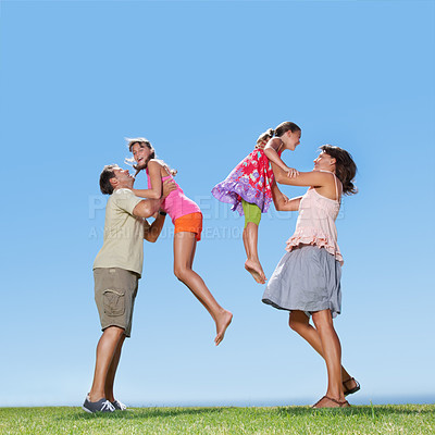Buy stock photo Full length of family enjoying outdoors with parents picking up their daughters