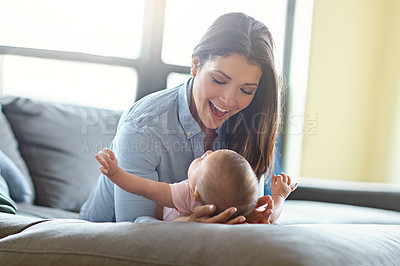 Buy stock photo Shot of a mother with her baby girl on the sofa at home