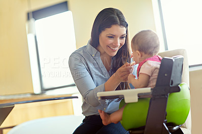 Buy stock photo Shot of a mother feeding her baby girl in a high chair