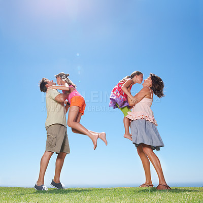 Buy stock photo Full length of family having fun outdoors with parents picking up their daughters