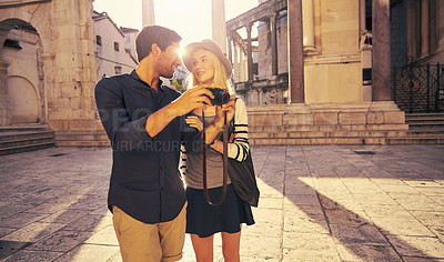 Buy stock photo Shot of a young couple taking pictures while walking through an old city