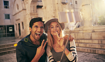 Buy stock photo Shot of a young couple taking a selfie with a selfie stick while walking through an old city