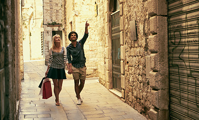 Buy stock photo Shot of a young couple walking through an old city