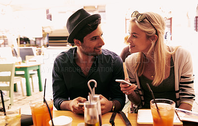 Buy stock photo Shot of a young couple spending time together at a cafe