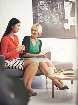 Buy stock photo Full length shot of two young businesswoman sitting on a sofa in the office