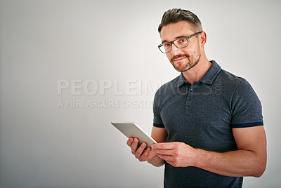 Buy stock photo Shot of a man using a digital tablet against a gray background