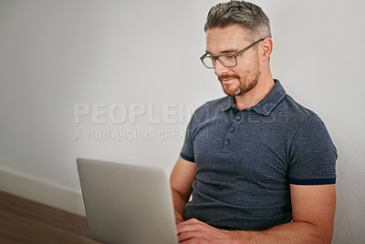 Buy stock photo Shot of a man using his laptop while sitting against a wall