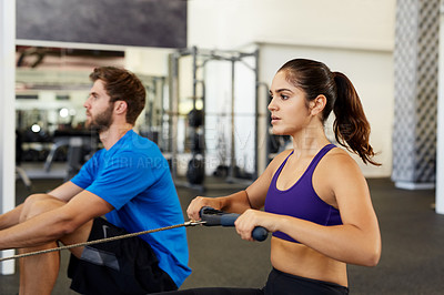 Buy stock photo Cropped shot of two young people using the rowing machines in the gym