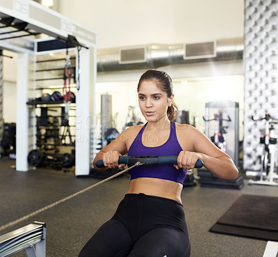 Buy stock photo Cropped shot of a young woman using the rowing machine in the gym