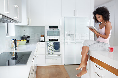 Buy stock photo Shot of a young woman using a digital tablet while sitting on her kitchen counter